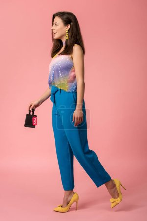 Photo pour Full length view of stylish disco girl holding shopping bag with sale lettering on label on pink - image libre de droit