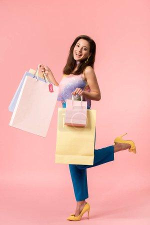 Photo pour Vue pleine longueur de fille disco élégant heureux posant avec des sacs à provisions sur rose - image libre de droit