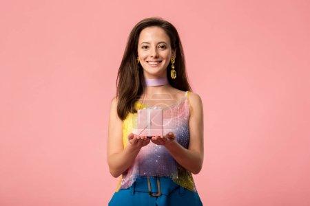 Photo pour Jolie jeune discothèque tenant une boîte-cadeau isolée en rose - image libre de droit