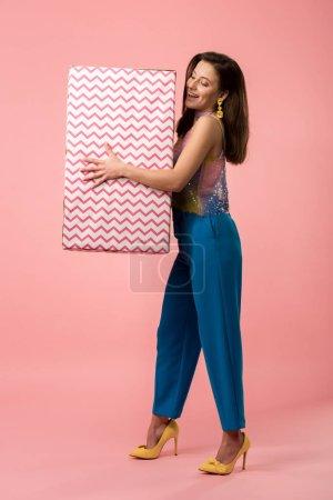 Photo pour Heureux jeune fille disco élégant tenant grande boîte cadeau sur rose - image libre de droit