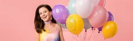 Foto de Panoramic shot of young smiling party girl holding festive balloons isolated on pink - Imagen libre de derechos