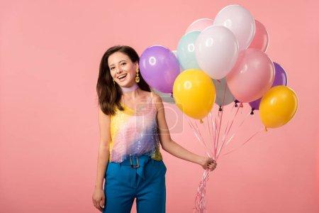 Photo pour Jeune joyeuse fille tenant des ballons de fête isolés sur le rose - image libre de droit