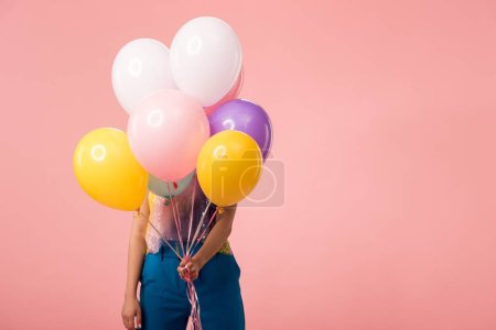Foto de Young party girl holding festive balloons in front of face isolated on pink - Imagen libre de derechos