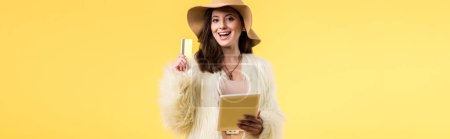 Photo for Panoramic shot of happy elegant girl in faux fur jacket and hat holding digital tablet and credit card isolated on yellow - Royalty Free Image