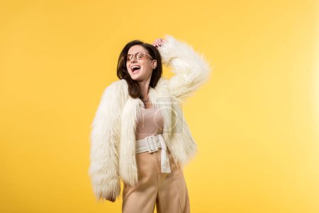 Photo pour Excited party girl in faux fur jacket and sunglasses dancing isolated on yellow - image libre de droit