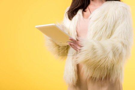Photo pour Crochet vue d'une élégante fille vêtue d'une fausse veste de fourrure utilisant une tablette numérique isolée sur jaune - image libre de droit