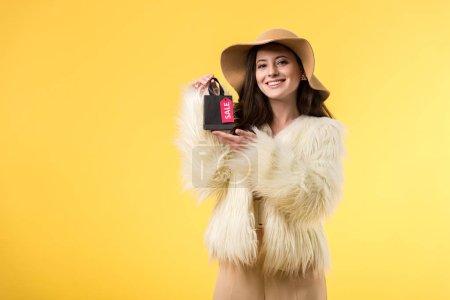 Photo pour Élégante fille souriante en fausse veste de fourrure et chapeau tenant un sac à provisions avec lettrage de vente isolée sur jaune - image libre de droit