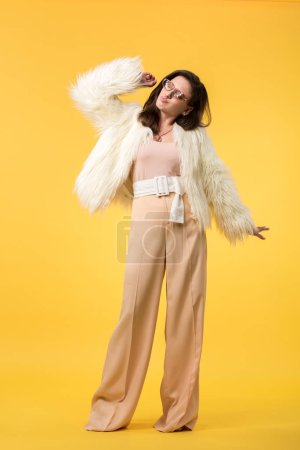 Photo pour Full length view of party girl in faux fur jacket and sunglasses dancing on yellow - image libre de droit