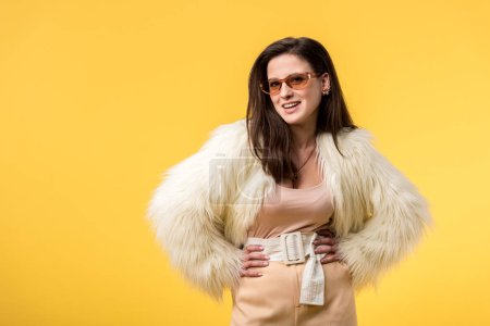Photo pour Smiling party girl in faux fur jacket and sunglasses with hands on hips isolated on yellow - image libre de droit