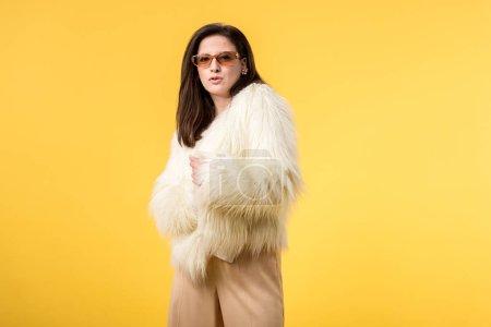 Photo pour Fille de fête élégante en fausse veste de fourrure et lunettes de soleil isolées sur jaune - image libre de droit