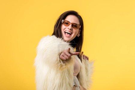 Aufgeregtes Partygirl in Kunstpelzjacke und Sonnenbrille zeigt mit dem Finger auf Kamera