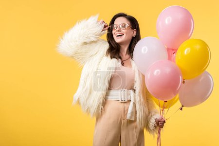 Photo pour Happy party girl in faux fur jacket and sunglasses holding ballons isolated on yellow - image libre de droit