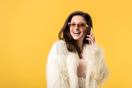 Photo pour Happy party girl in faux fur jacket and sunglasses talking on smartphone isolated on yellow - image libre de droit