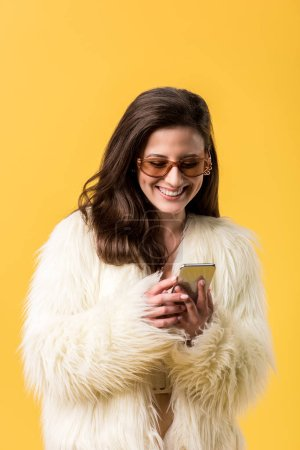 Photo pour Happy party girl in faux fur jacket and sunglasses using smartphone isolated on yellow - image libre de droit