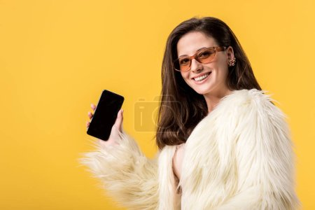 Photo for Happy party girl in faux fur jacket and sunglasses holding smartphone with blank screen isolated on yellow - Royalty Free Image