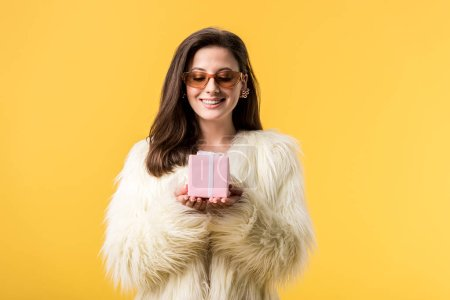 Photo pour Happy party girl in faux fur jacket and sunglasses looking at gift box isolated on yellow - image libre de droit