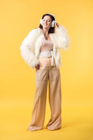Photo pour Vue pleine longueur d'une fille souriante en fausse veste de fourrure écoute de la musique dans les écouteurs isolés sur jaune - image libre de droit