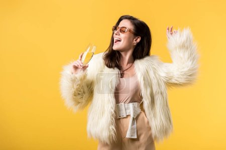 Photo pour Happy party girl in faux fur jacket and sunglasses dancing with champagne isolated on yellow - image libre de droit