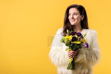 Photo pour Jeune fille souriante en fausse veste de fourrure tenant bouquet de fleurs isolé sur jaune - image libre de droit