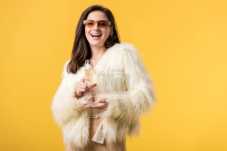 Photo pour Excited party girl in faux fur jacket and sunglasses with champagne isolated on yellow - image libre de droit