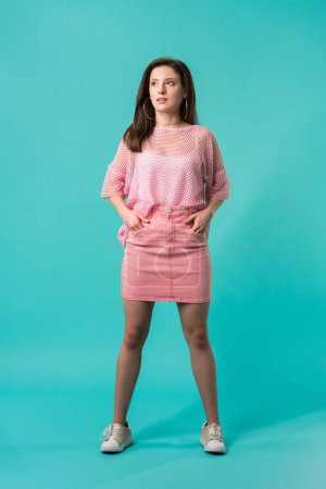 Photo for Girl in pink outfit standing with hands on hips and looking away on turquoise background - Royalty Free Image