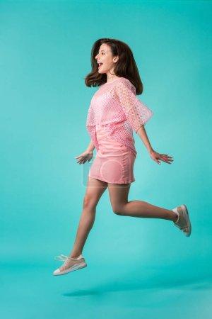 Photo pour Excitée fille en tenue rose sautant sur fond turquoise - image libre de droit