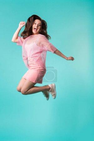 Foto de Jovencita apasionada con boca abierta en traje rosa saltando aislada sobre turquesa. - Imagen libre de derechos