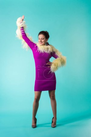 Photo pour Happy party girl in purple dress with feathers dancing on turquoise background - image libre de droit