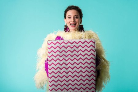 Photo pour Happy party girl in purple dress with feathers holding huge gift box isolated on turquoise - image libre de droit