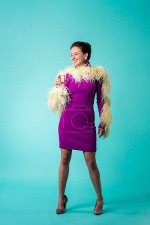 Photo pour Happy party girl en robe violette avec des plumes tenant un verre de champagne sur turquoise - image libre de droit