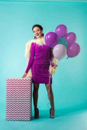 Photo pour Happy party girl in purple dress with feathers holding ballons near huge gift box on turquoise - image libre de droit