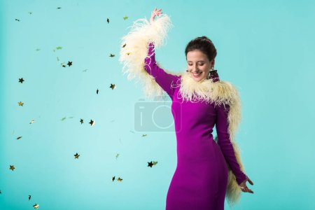 Photo pour Happy party girl in purple dress with feathers dancing under falling confetti isolated on turquoise - image libre de droit