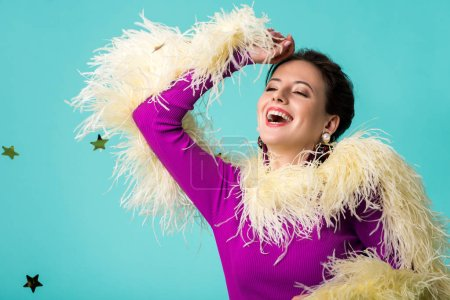 Photo pour Happy party girl in purple dress with feathers under falling confetti isolated on turquoise - image libre de droit