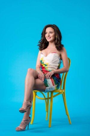 Photo pour Souriant élégante jeune femme en robe assise sur une chaise jaune et regardant loin sur fond bleu - image libre de droit