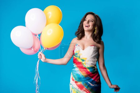 Photo pour Happy elegant young woman in dress holding balloons isolated on blue - image libre de droit