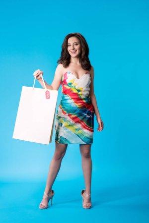 Photo pour Une élégante jeune femme souriante en robe tenant un sac à provisions sur fond bleu - image libre de droit