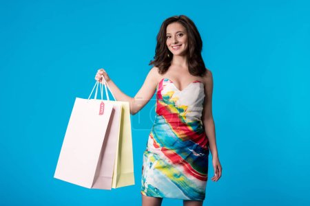 Photo for Smiling elegant young woman in dress holding shopping bags isolated on blue - Royalty Free Image