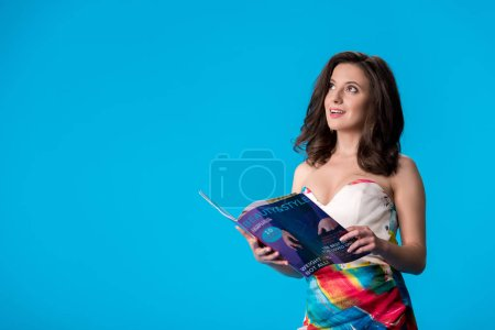 Photo for Dreamy elegant young woman in dress holding style and beauty magazine isolated on blue - Royalty Free Image