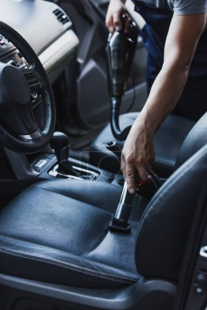 Photo for Partial view of car cleaner vacuuming drivers seat in car - Royalty Free Image