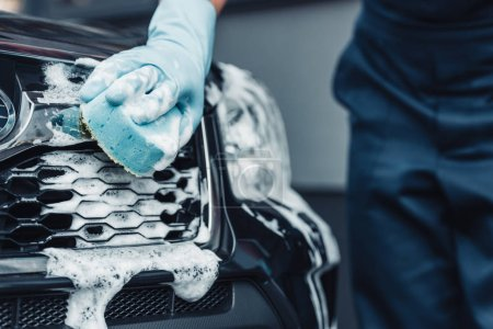 Photo pour Partial view of car cleaner washing car with sponge and detergent - image libre de droit