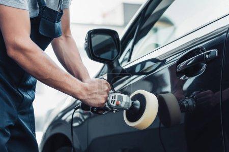 Photo pour Vue partielle du nettoyage de la voiture polissage de la porte de voiture avec machine tampon - image libre de droit