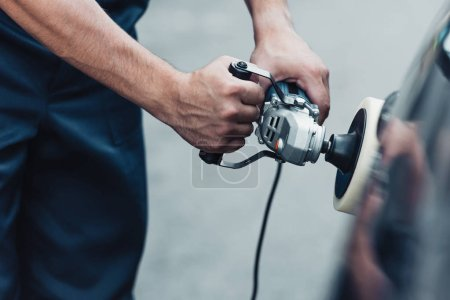 Teilansicht von Autoputzer poliert Auto mit Puffermaschine
