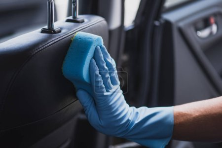 Photo pour Partial view of car cleaner in rubber glove wiping car seat - image libre de droit