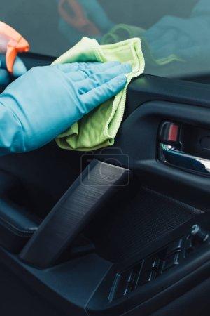 Photo pour Vue en coupe du nettoyant de voiture essuyant la porte de voiture avec chiffon - image libre de droit