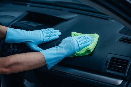 Photo pour Vue en coupe d'un nettoyant de voiture essuyant la planche de bord avec chiffon - image libre de droit
