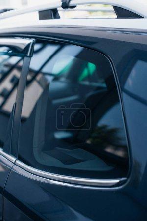 Photo pour Fenêtre latérale d'une voiture noire, moderne, polie et réfléchissante - image libre de droit