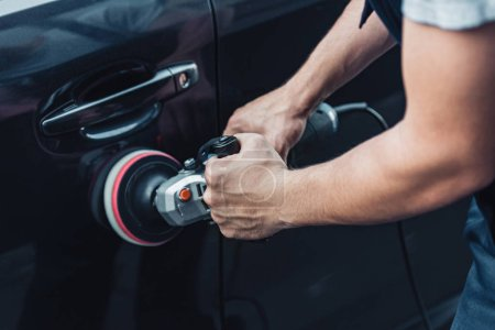 Photo for Partial view of car cleaner polishing black car door with buffer machine - Royalty Free Image