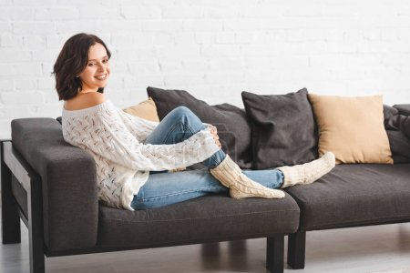 Photo pour Attractive brunette woman sitting on sofa with pillows in cozy living room - image libre de droit
