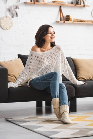 Photo for Happy beautiful woman sitting on sofa in cozy living room - Royalty Free Image
