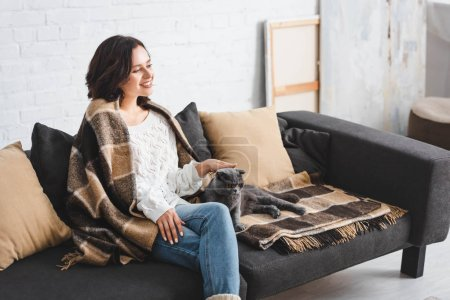 Photo pour Happy girl in blanket sitting on sofa with scottish fold cat - image libre de droit